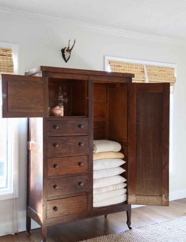 A white living room with a dark wood cabinet filled with linen organization