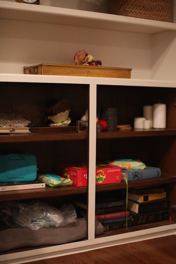 Built in cabinets filled with clutter in the before image of a makeover.