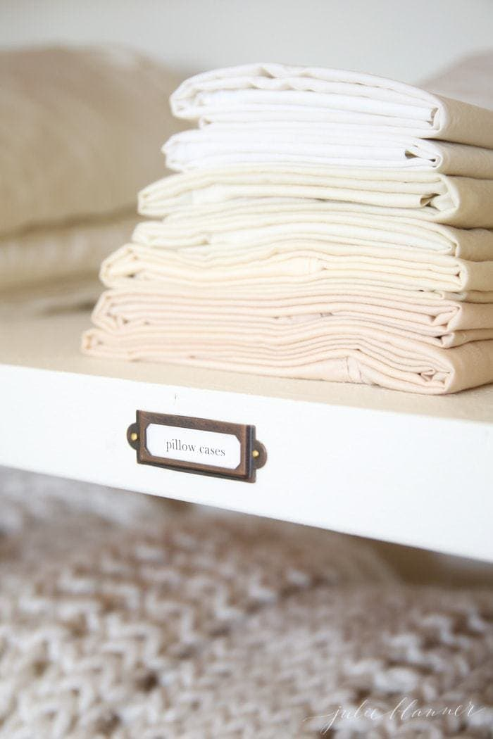 A stack of white and ivory sheet sets in a hallway linen closet.