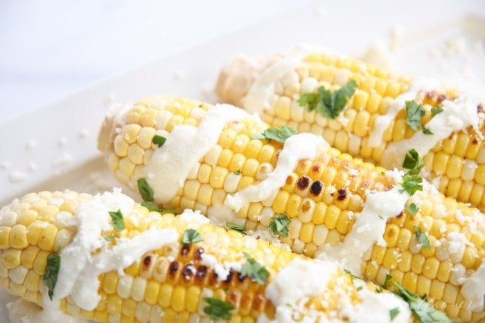 Mexican corn on the cob on a white platter.