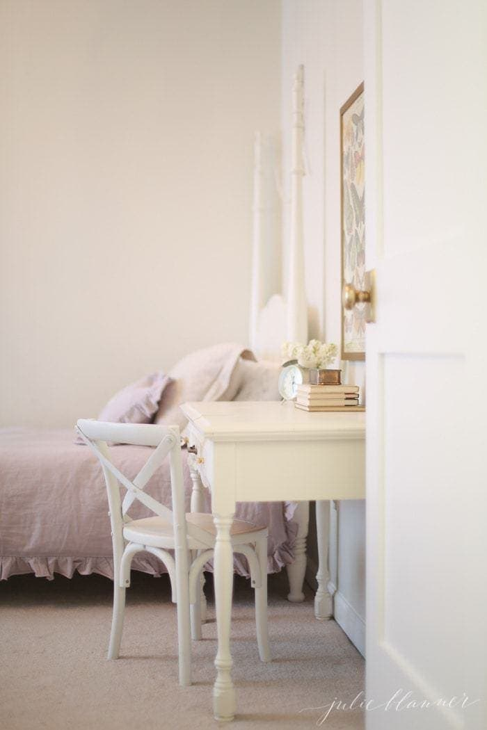 A white kids bedroom with a desk as a bedside table, pink chair.