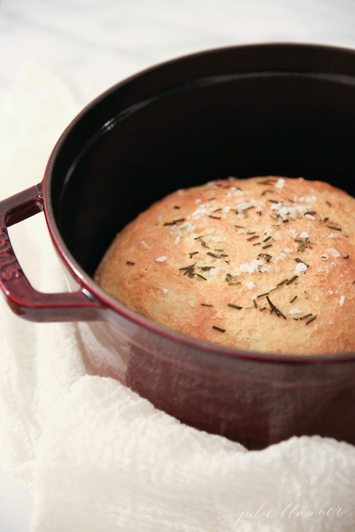 baked homemade bread with sea salt and rosemary in a brown dutch oven