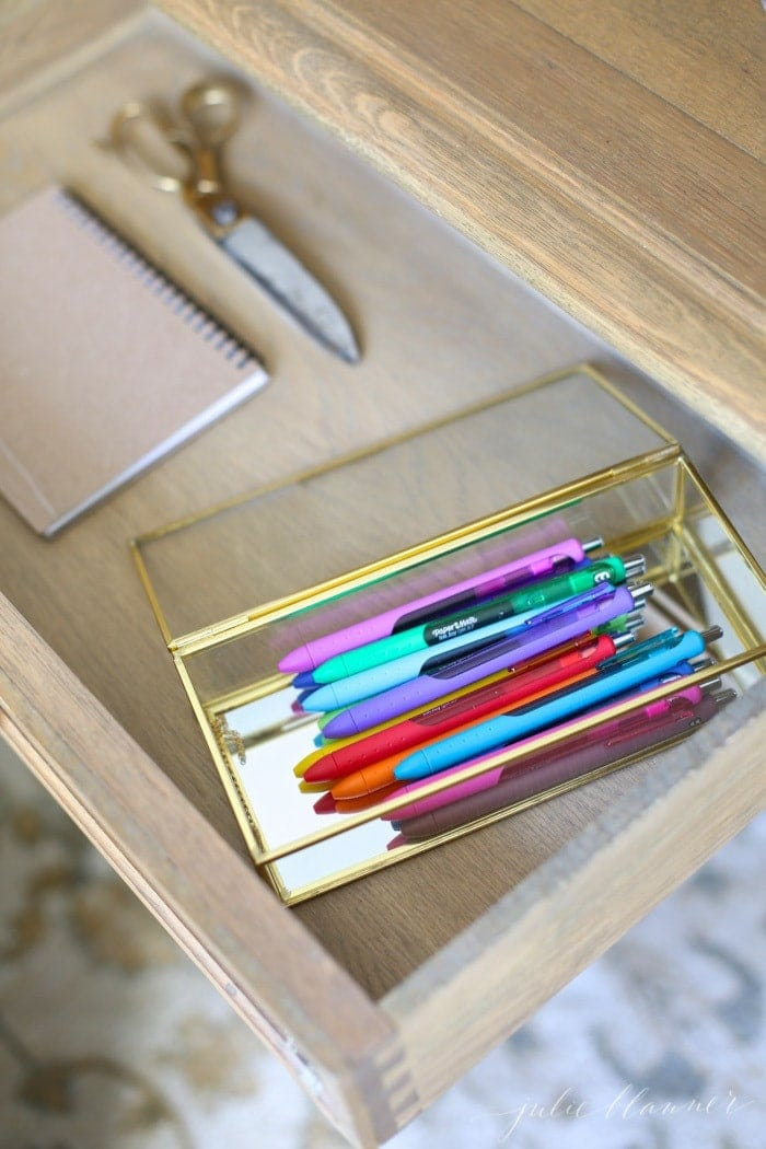Looking inside a wood desk that is carefully organized, pens in a pretty glass box.