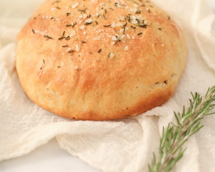 Homemade bread on a white kitchen towel with rosemary sprig