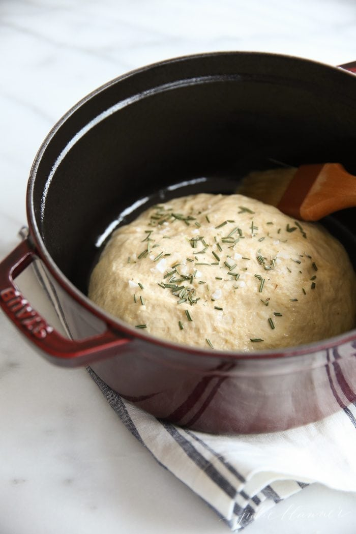 artisan bread dough in a brown dutch oven with pastry brush