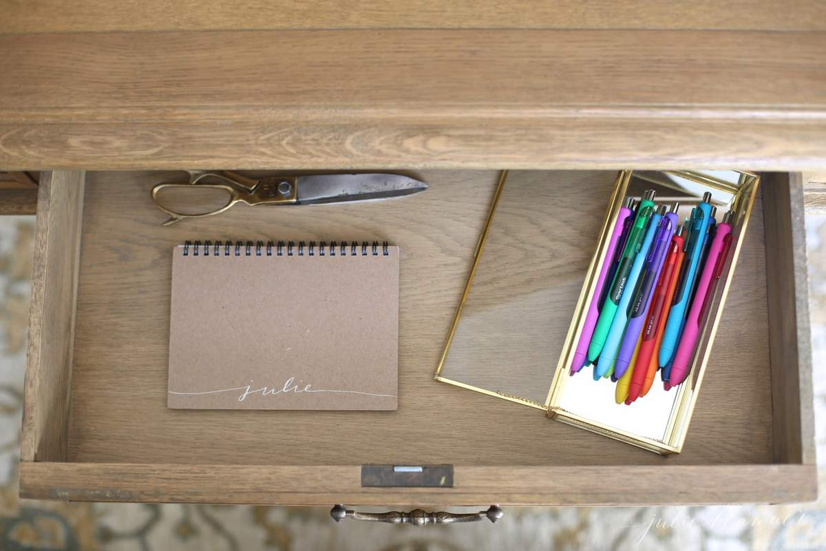 Inside a clean wooden desk drawer, organized notebook, scissors and a gold case full of pens.