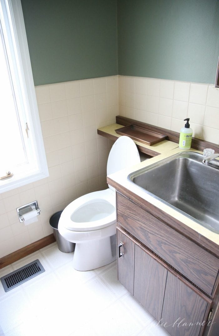 an image of a dated powder room with a large stainless steel sink.