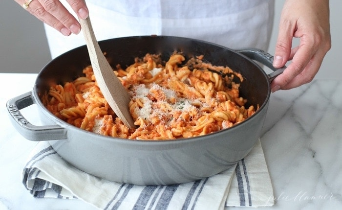 A wooden spoon stirring vodka sauce into pasta