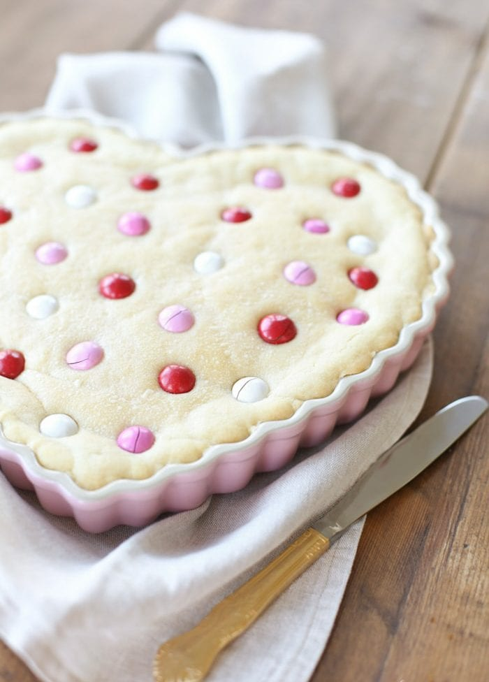 A sugar cookie cake in a heart shaped dish
