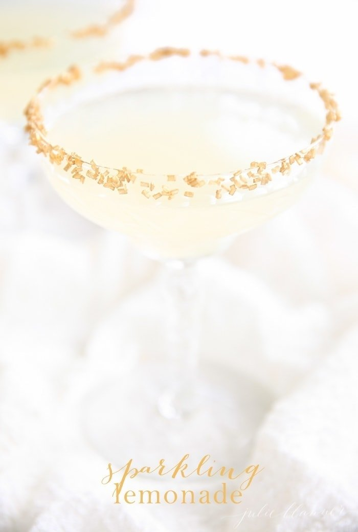 A sparkling lemonade cocktail with a gold rim, white background