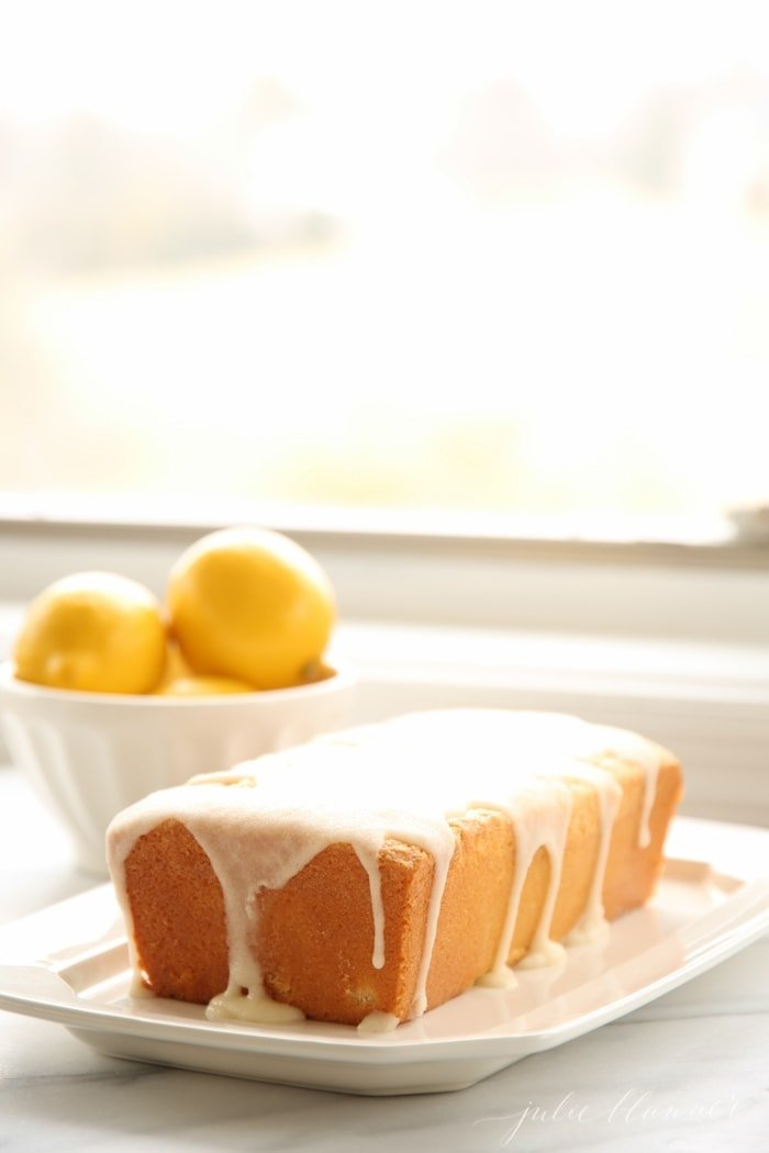 lemon pound cake with a lemon glaze on top, bowl of lemons in the background