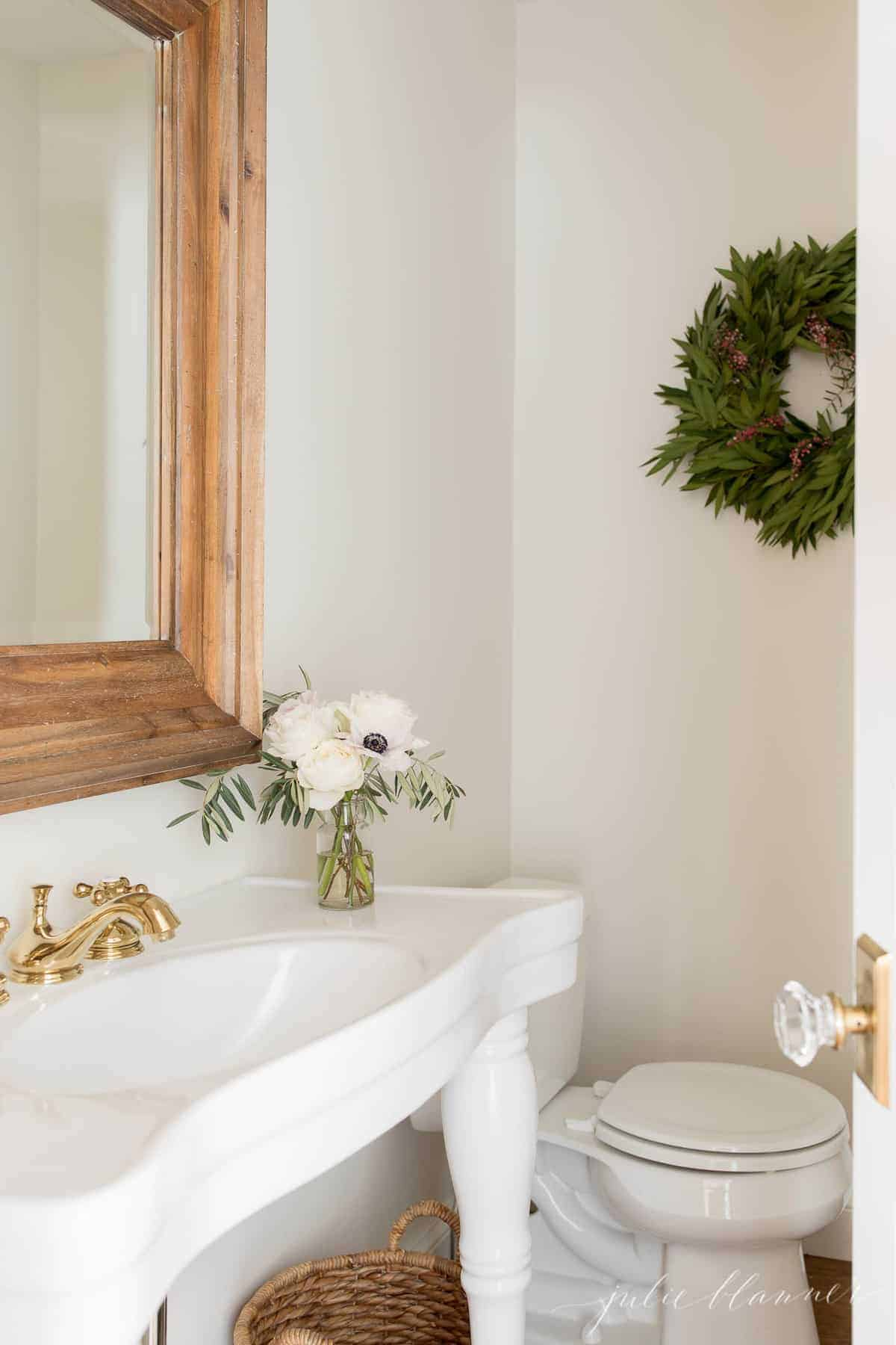 traditional bathroom with white sink wood mirror and christmas wreath