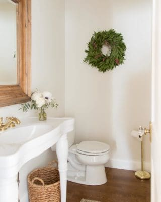 bathroom decorated for christmas with woven wastebasket parisian sink and turkish rug