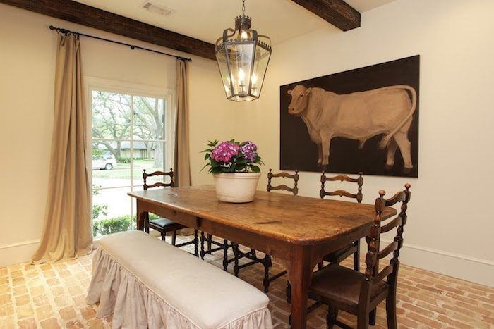 breakfast nook with cow painting, lantern, beams, brick floors, wood table