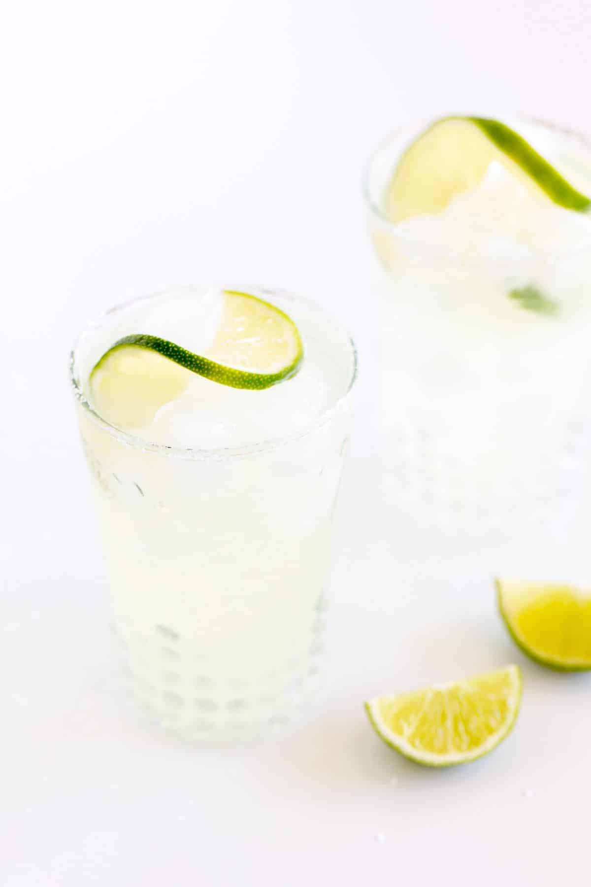 clear glasses full of a margarita from scratch, garnished with lime and lime wedges to the side.