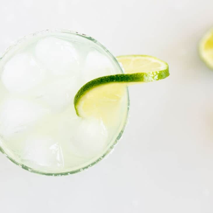 A clear glass with a homemade margarita, rimmed with salt and a slice of lime on a white background.