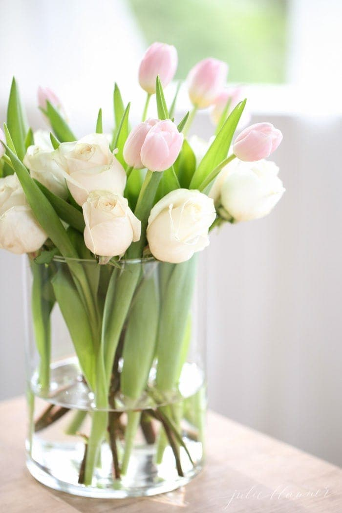 A cylinder glass vase filled with pink tulips and white roses.