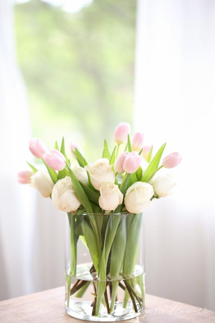 A clear cylinder vase filled with pink tulips and white roses