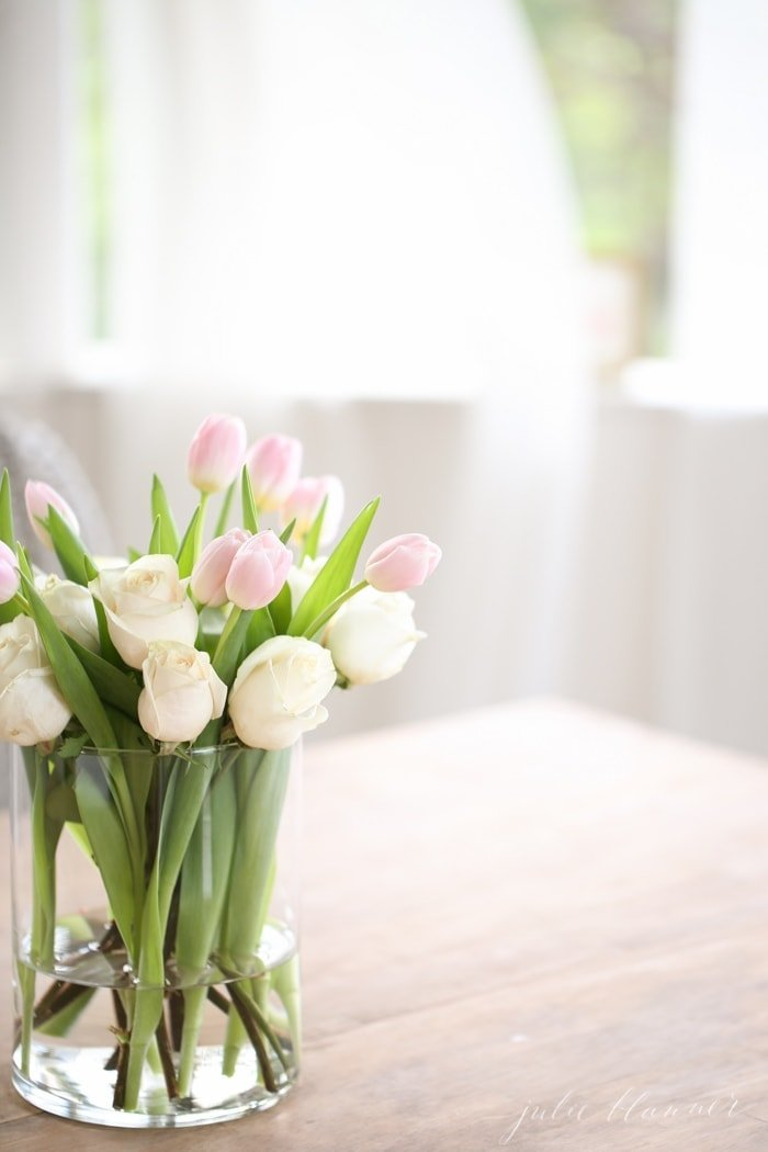 an arrangement of pink tulips and white roses in a cylinder vase.