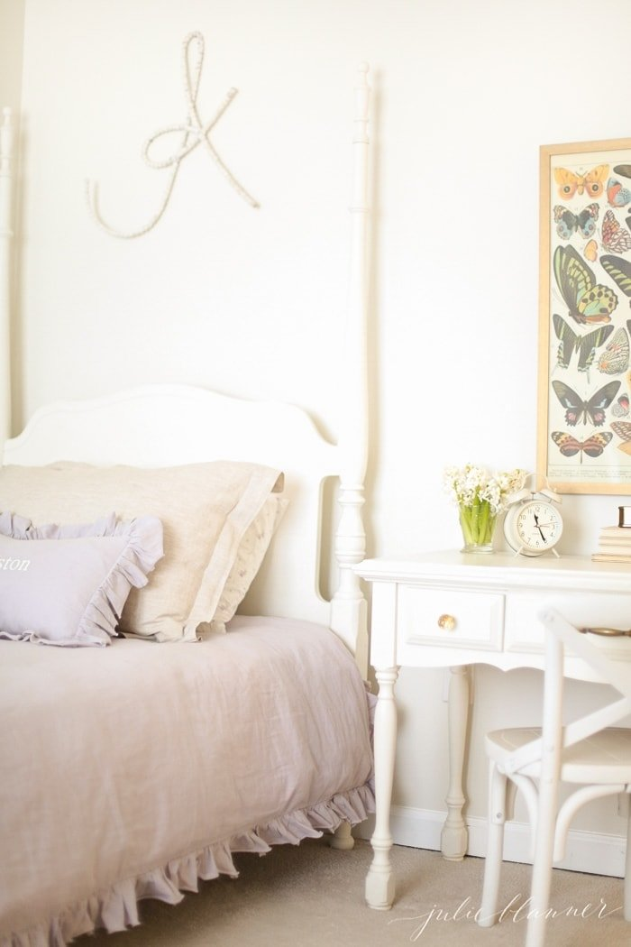 A white bedroom for a little girl with a white four poster bed and a large letter A above the headboard.