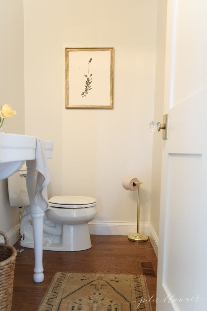 Looking into a white guest bathroom with a kilim turkish rug on the floor.
