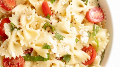 bow tie pasta salad in a bowl with cherry tomatoes basil and feta