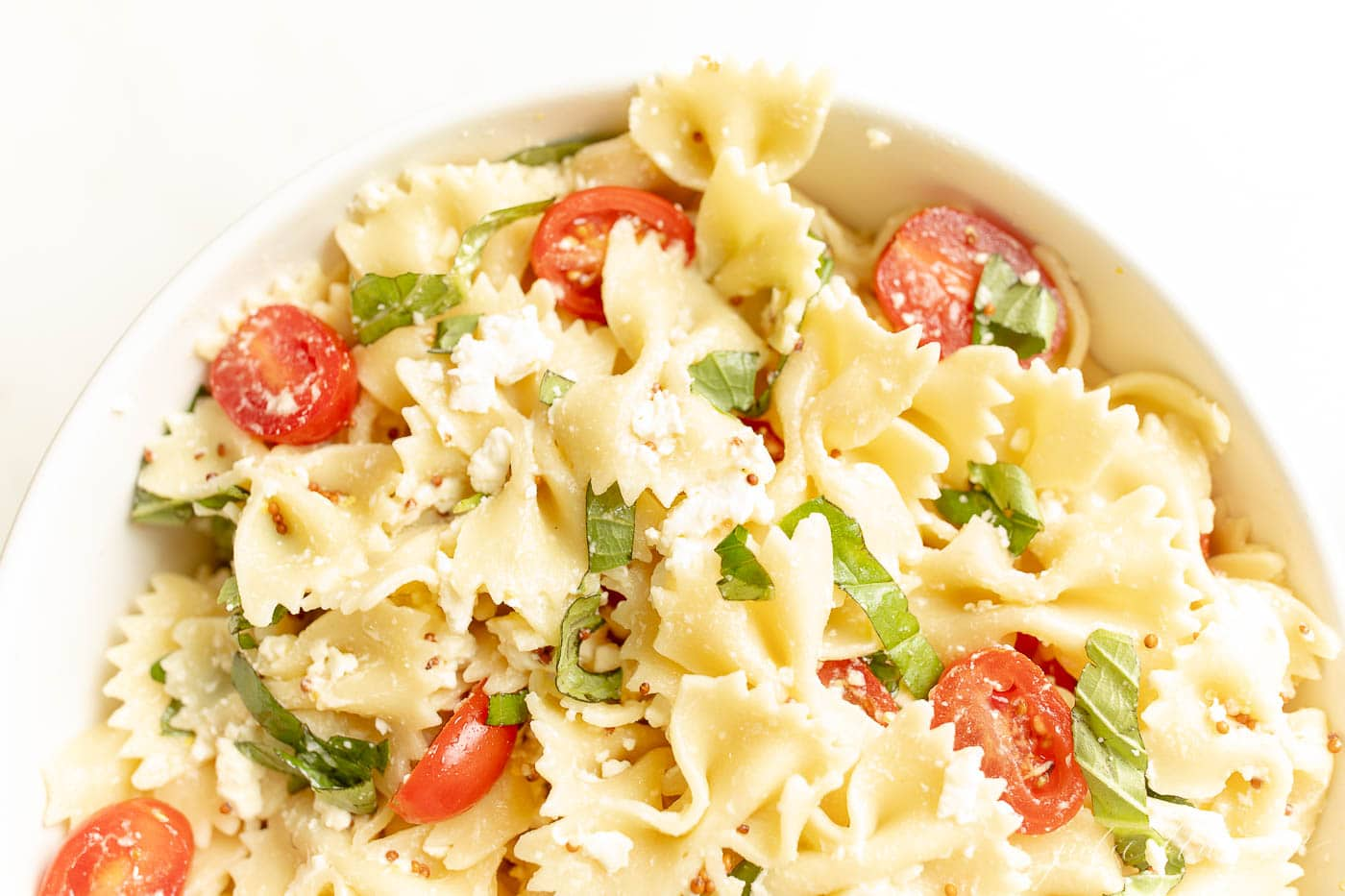 easy pasta salad recipe in a bowl with tomato and basil