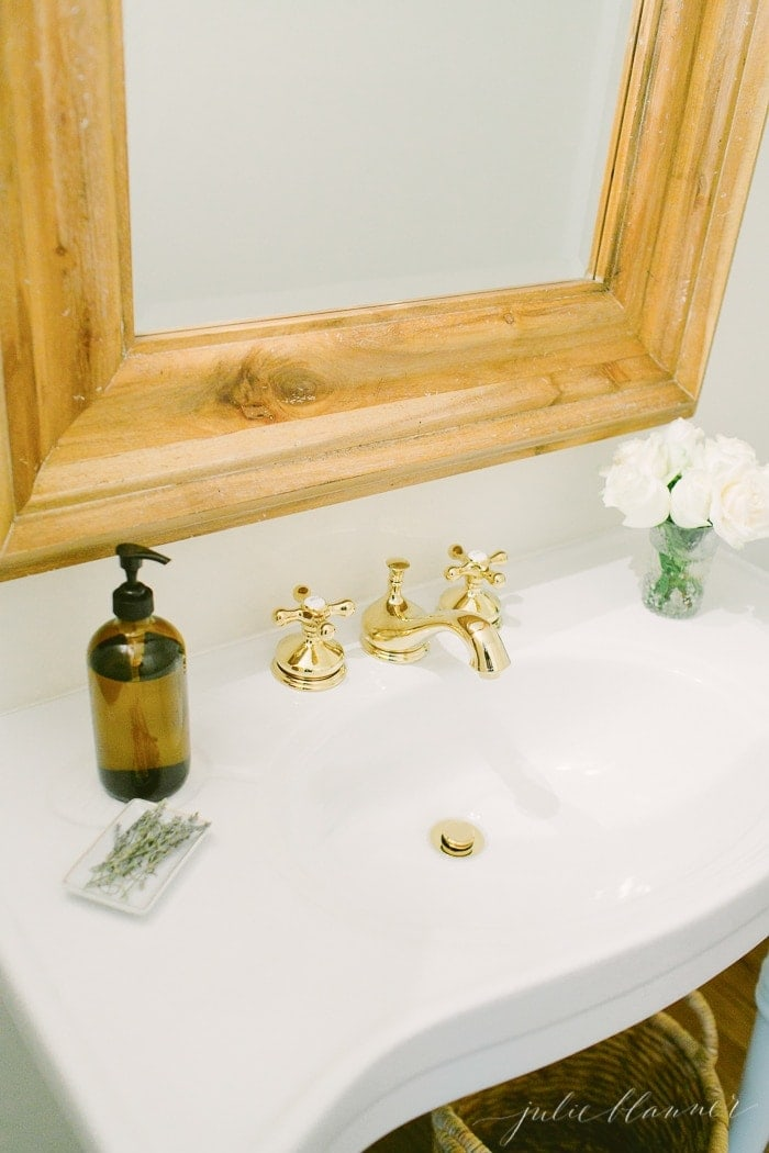 beautiful bathroom with wood mirror, parisian sink and brass faucet