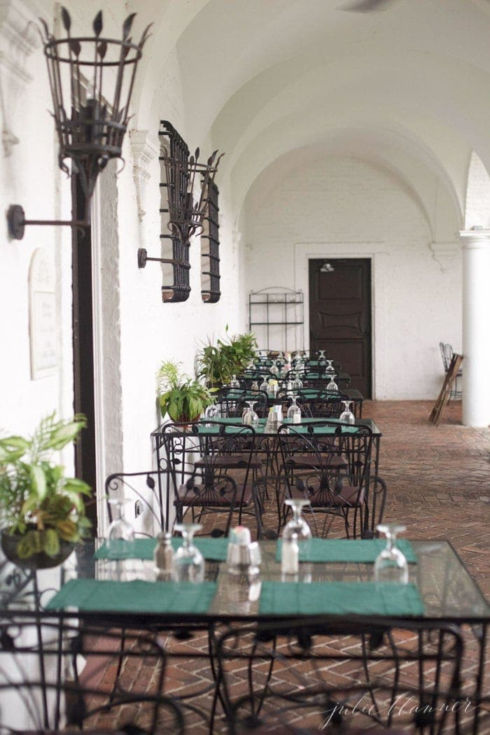 Black iron tables and chairs on a brick patio at a restaurant in Jekyll Island Georgia