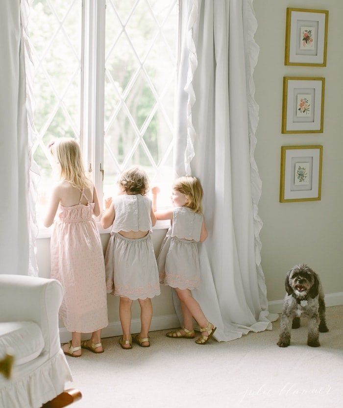 Three little girls looking out a window in a white kids bedroom, dog to the side.