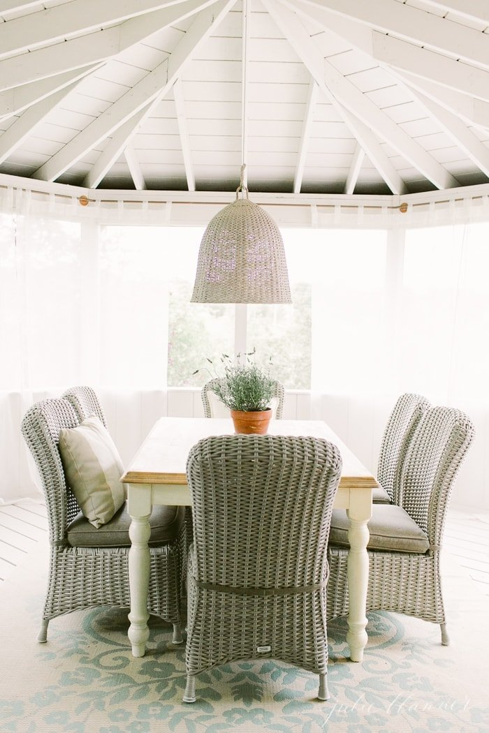 A screened in porch with white sheer curtains and a wicker patio dining set.