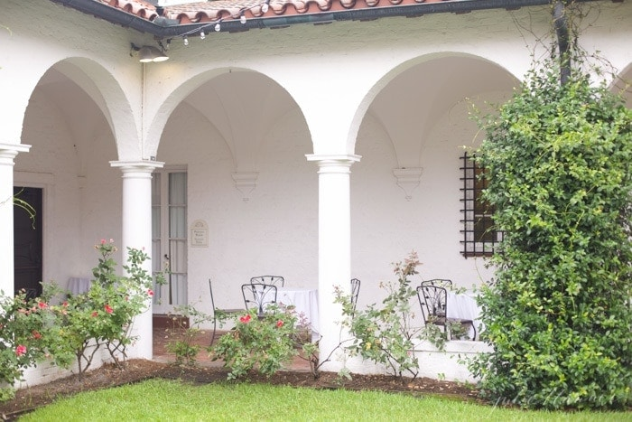 A Spanish inspired southern building with arched doorways and shutters.