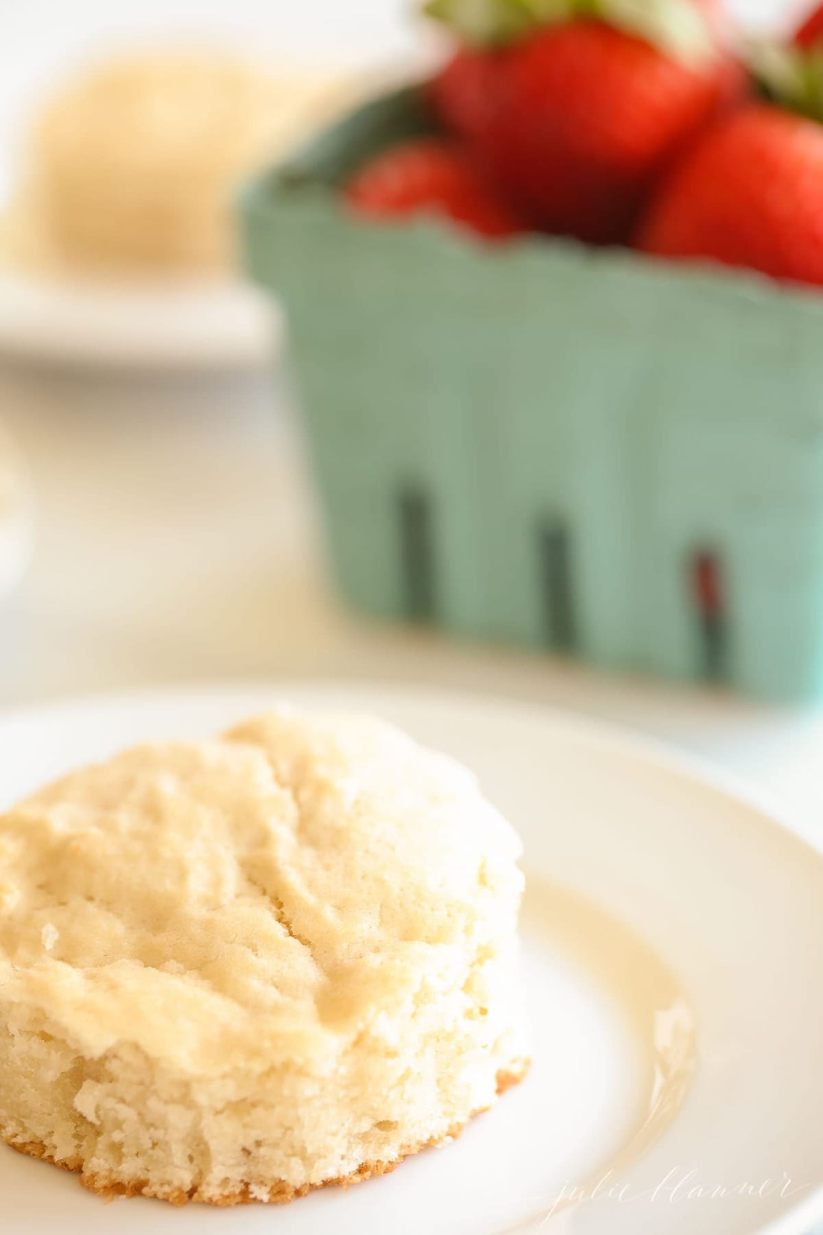 A cutout strawberry shortcake biscuit, with a turquoise carton of strawberries behind.