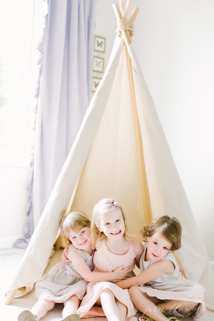 Three little girls inside a homemade canvas teepee.