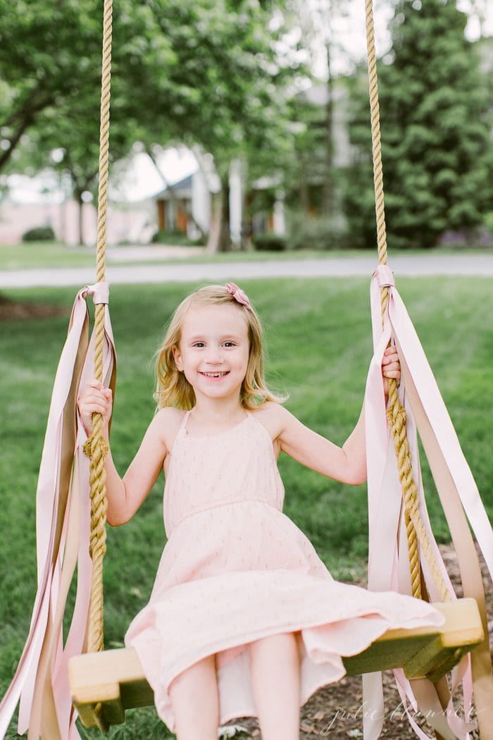 girl on wood tree swing with ribbons tied on it