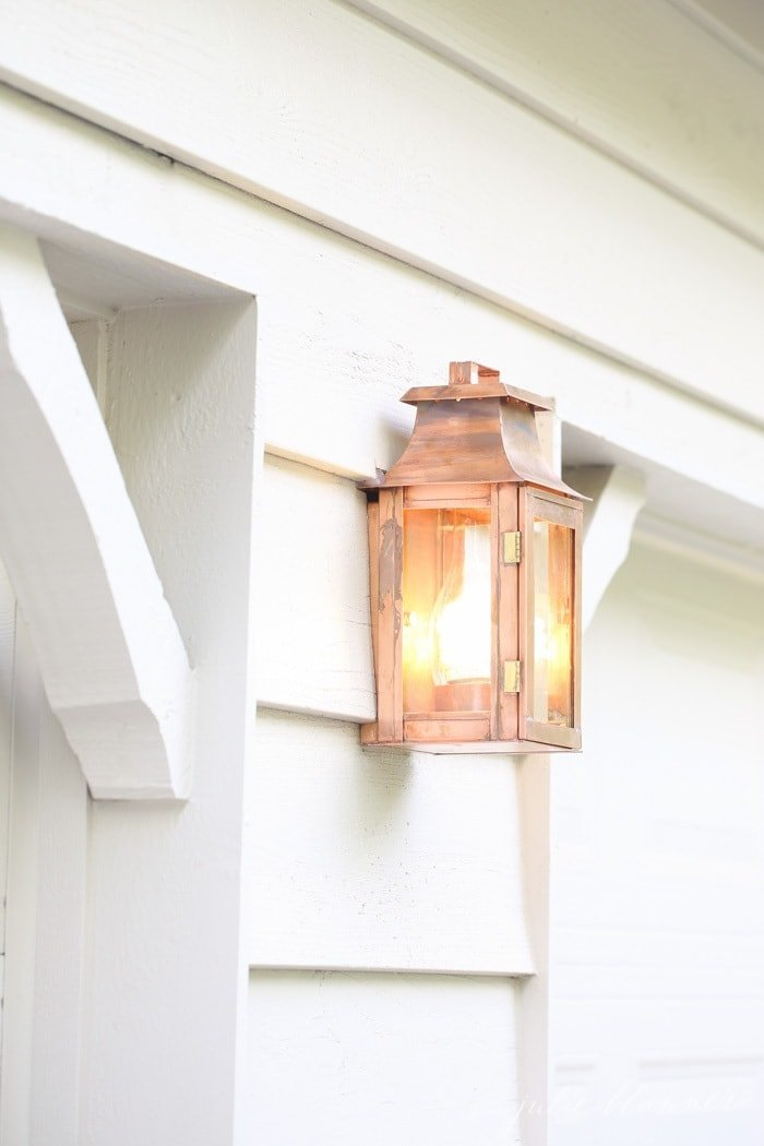 A white home exterior with a copper lantern in between garage doors.
