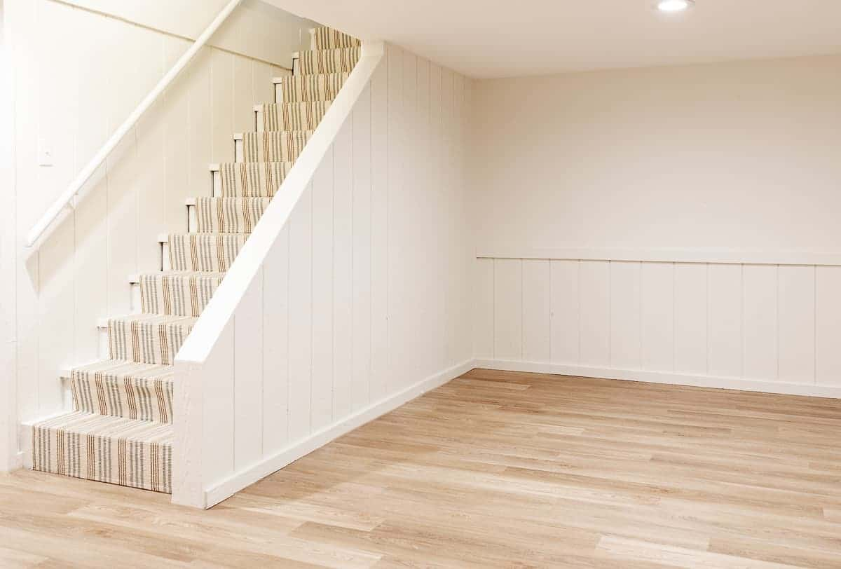 neutral room with stairs covered with stripe stair runner