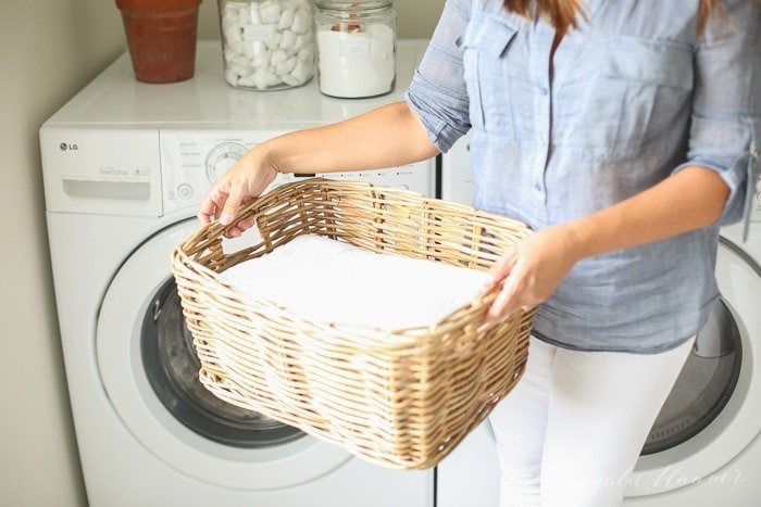 woman carrying basket of laundry in front of laundry machine