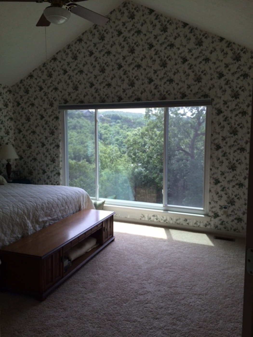 A dark bedroom with dated wallpaper on the walls a large windows.