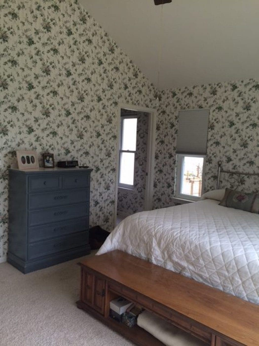 A dark bedroom with dated wallpaper on the walls and several windows.