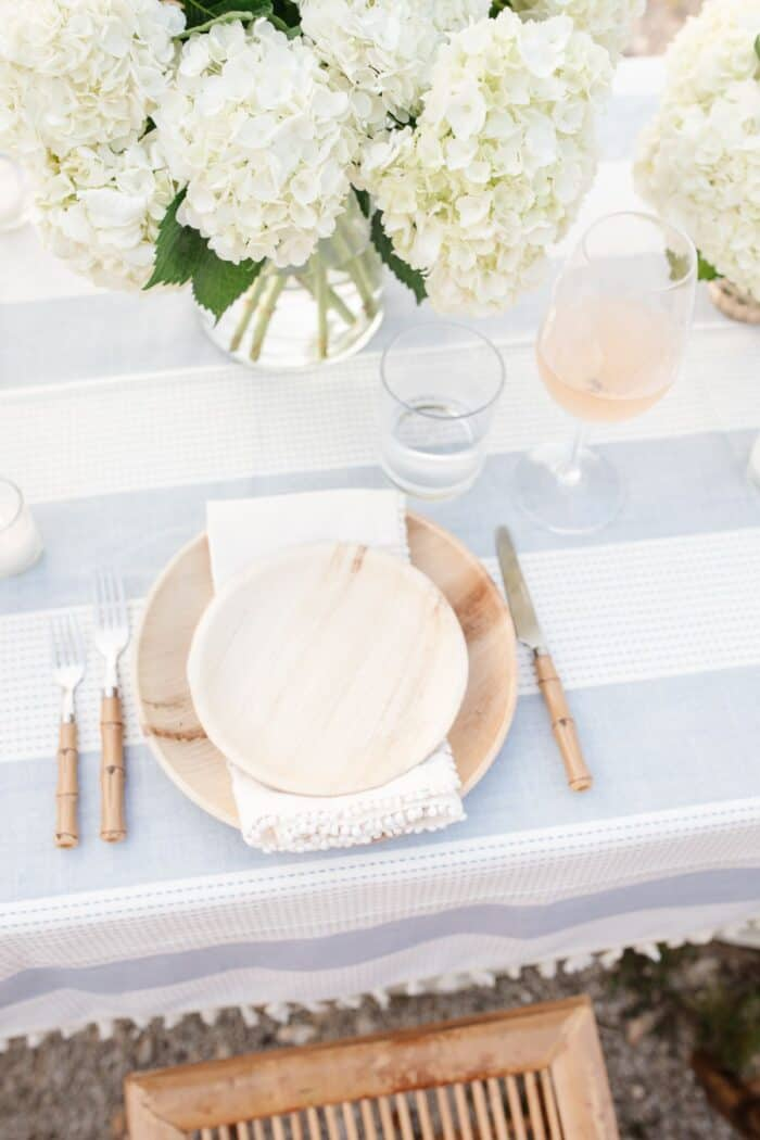 A wooden plate and charger with white flowers on a blue and white tablecloth for dinner al fresco.
