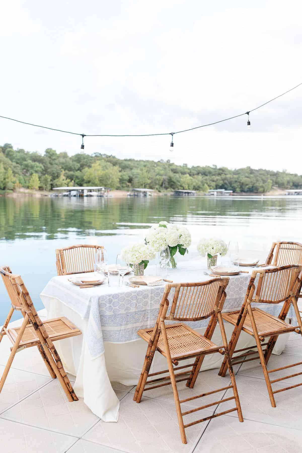 An al fresco dining table set with white flowers and a blue and white table cloth, water in the background.