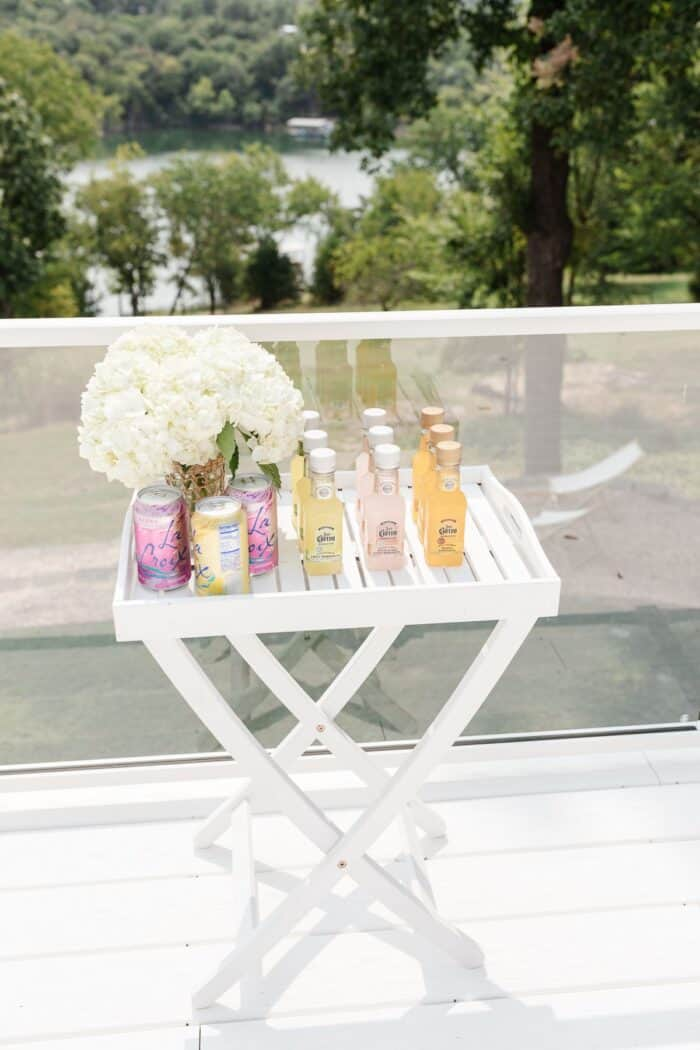 A small white dinner set up with small margarita jars for al fresco dining
