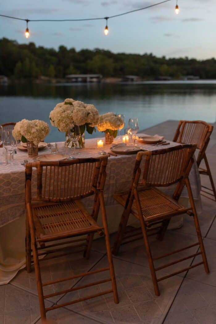 A table set with rattan folding chairs and white flowers for dinner al fresco on a dock.