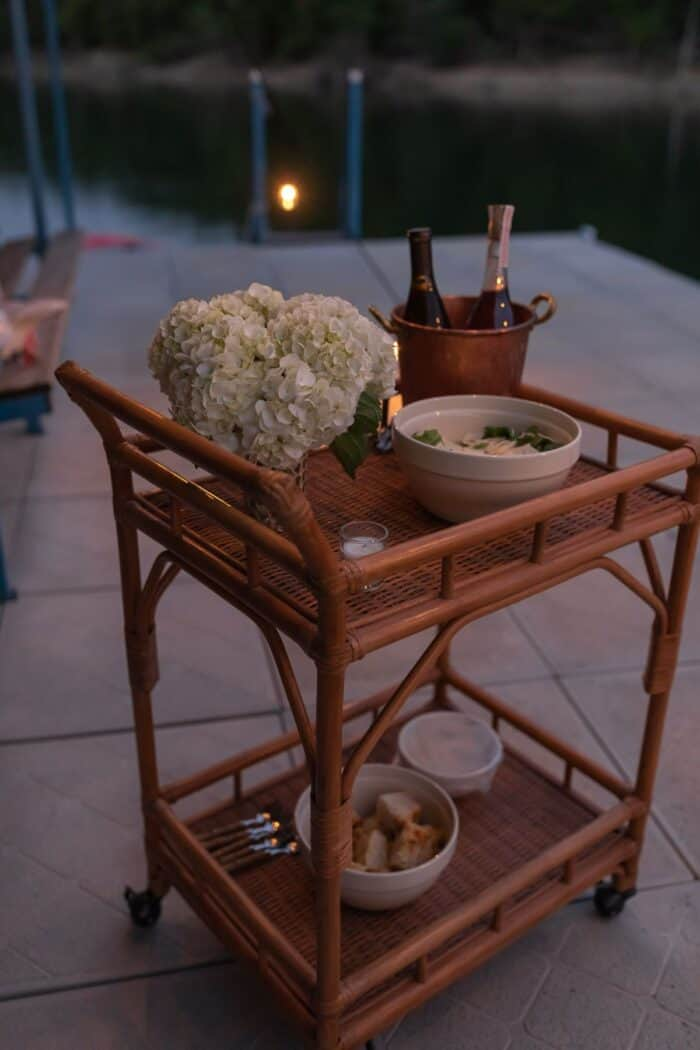A small rattan bar cart set up for al fresco dining on a dock.