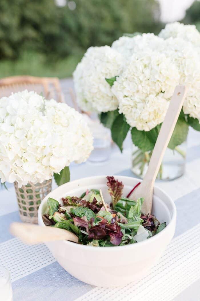 White hydrangea vases next to a salad bowl set up for dinner al fresco