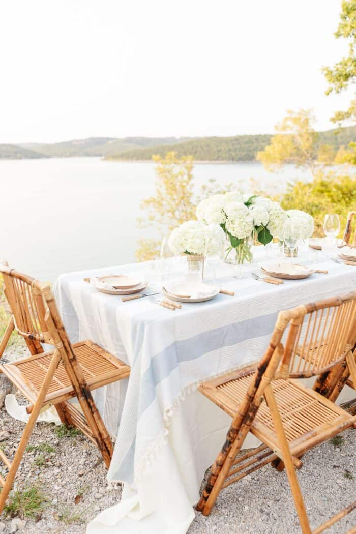 A table set up with bamboo dining chairs and water views for al fresco dining.
