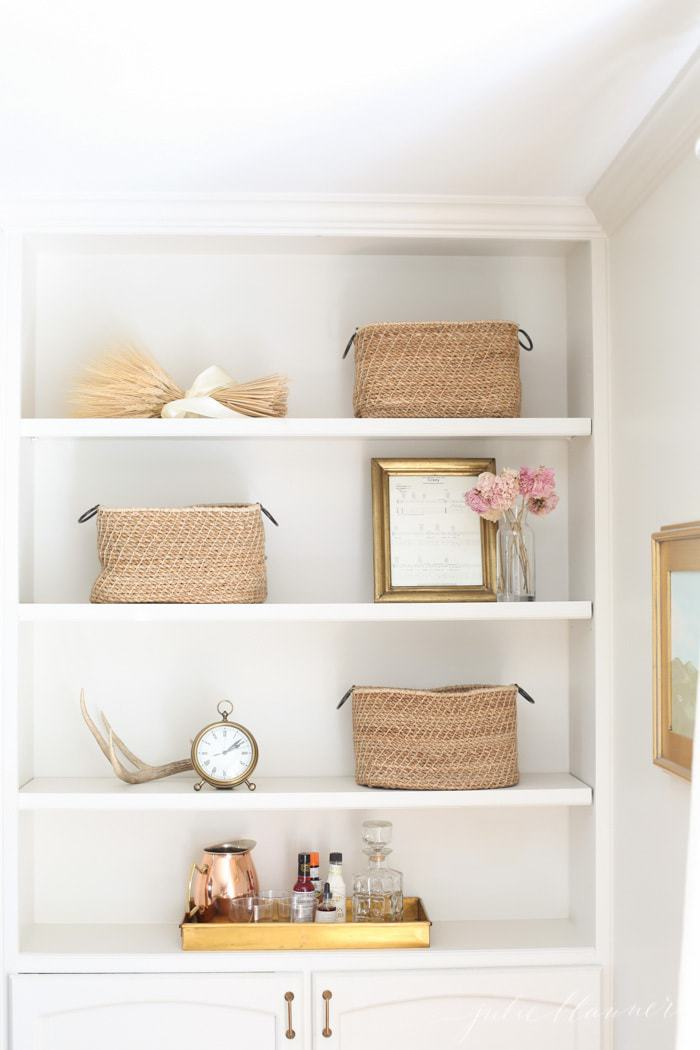 White bookshelves in a living room styled with baskets and accessories