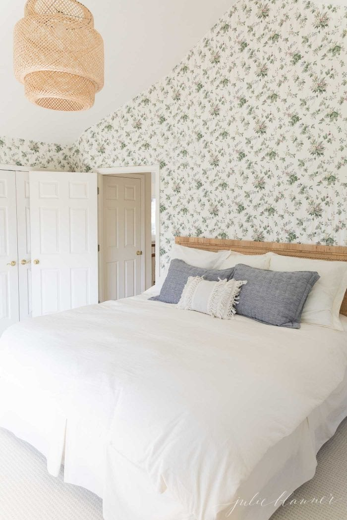 A bedroom with old wallpaper on the walls in a floral pattern, white bedding on the bed.