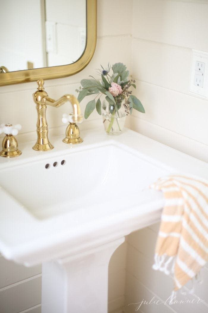 A white bathroom sink with gold faucet and mirror above.